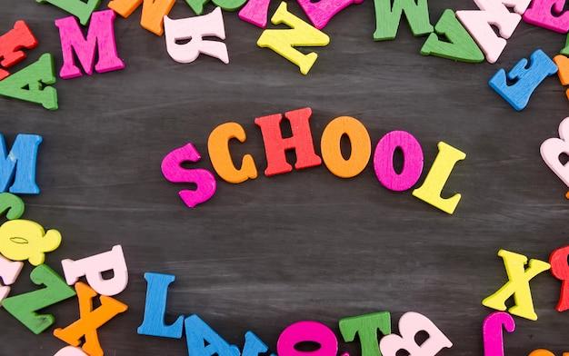 Escuela de palabras de letras de colores sobre un fondo de madera negra