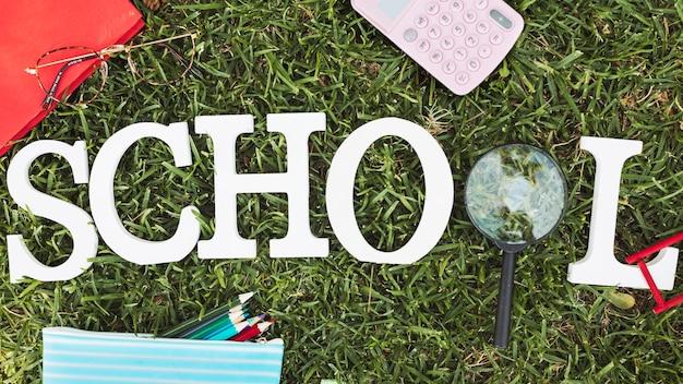Escuela de palabras con lupa y papelería sobre hierba.