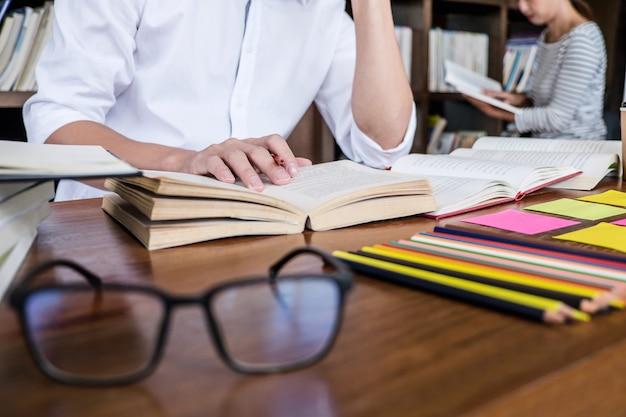 Escuela secundaria o grupo de estudiantes universitarios sentados estudiando y leyendo, haciendo la tarea