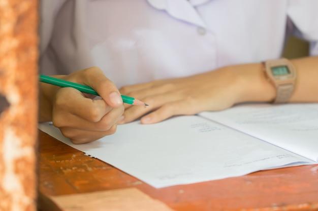 Escuela / universidad manos de estudiantes que toman exámenes, escribiendo sala de examen con un lápiz en la hoja