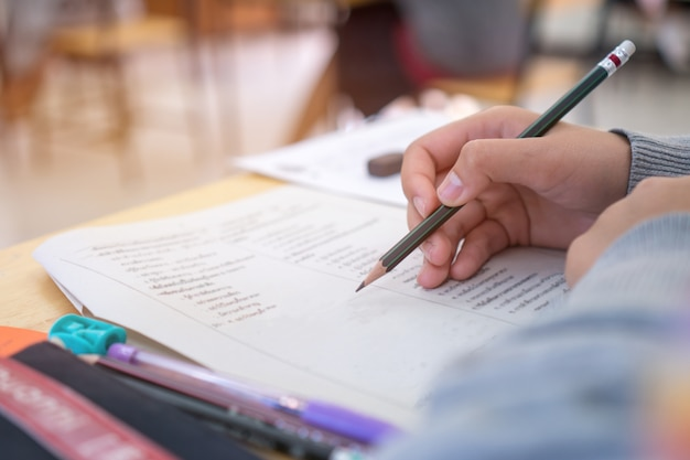 Escuela / universidad manos de estudiantes que toman exámenes, escribiendo sala de examen con lápiz de sujeción