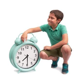 Las escuelas comienzan demasiado temprano. niño con gran despertador.
