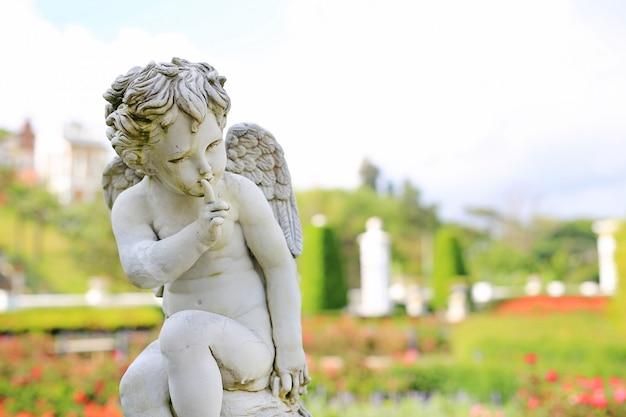 Escultura de cupido en jardín de verano al aire libre.