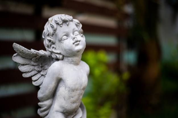Escultura de cupido de primer plano en el jardín