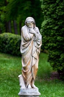 Escultura de mármol del parque de un anciano congelado y envuelto en colchas que personifican la estación fría del año