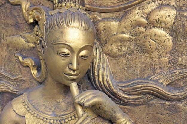 Escultura tailandesa de la cultura nativa en la pared del templo