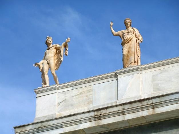 Esculturas de mármol del dios griego y la diosa contra el cielo azul, edificio histórico en atenas, grecia