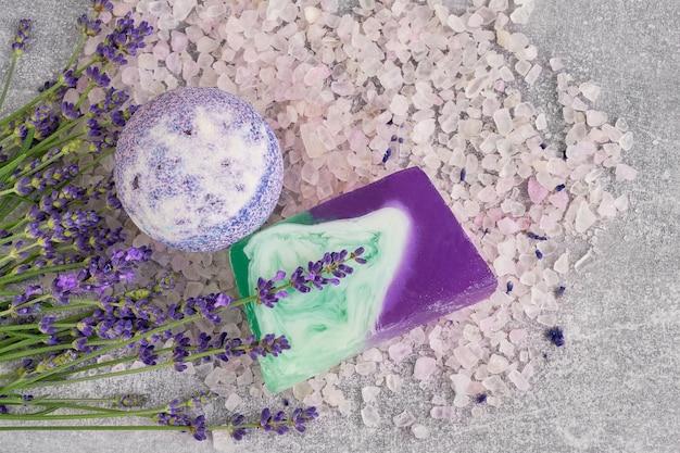 Esencial de sal lavanda, jabón y bomba de baño con flores vista superior. productos de lavanda spa.
