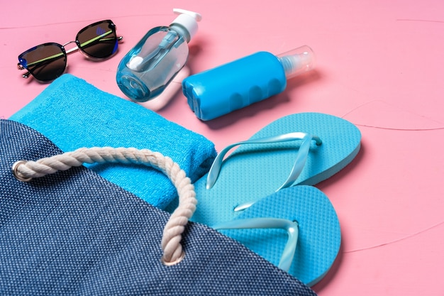Esenciales de playa y bolso de playa azul sobre fondo rosa