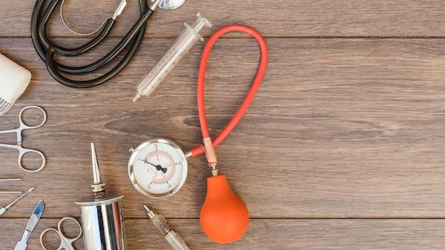 Esfigmomanómetro; estetoscopio y equipos médicos en el mostrador de madera.