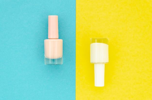 Esmalte de uñas blanco sobre fondo amarillo y azul