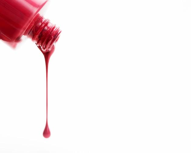 Esmalte de uñas brillante rojo que vierte en el fondo blanco