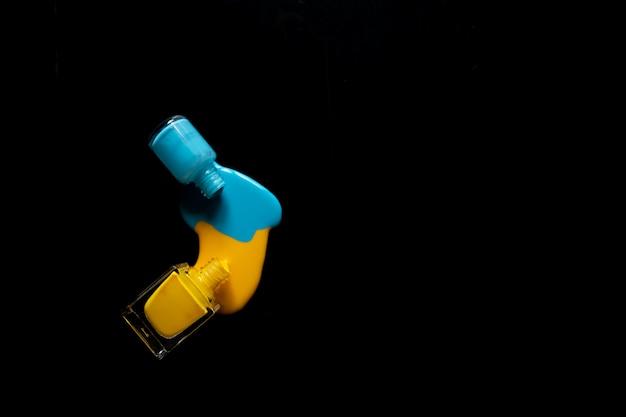 Esmalte de uñas derramado aislado sobre fondo negro, trazado de recorte incluido