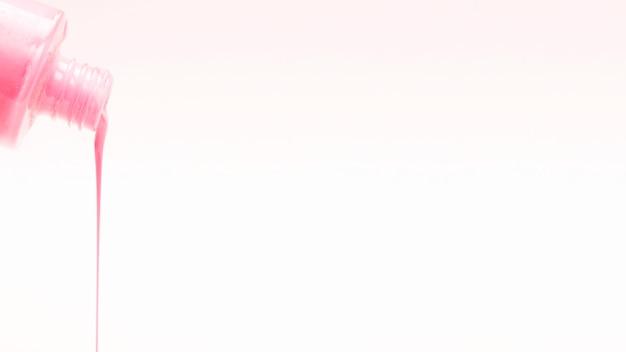 Esmalte de uñas rosado que vierte en el fondo blanco
