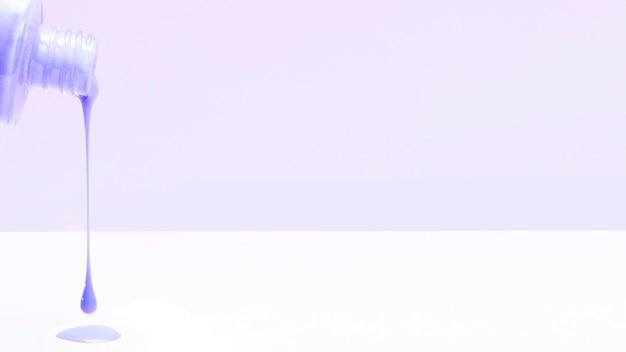 Esmalte de uñas violeta que gotea de la botella sobre fondo blanco
