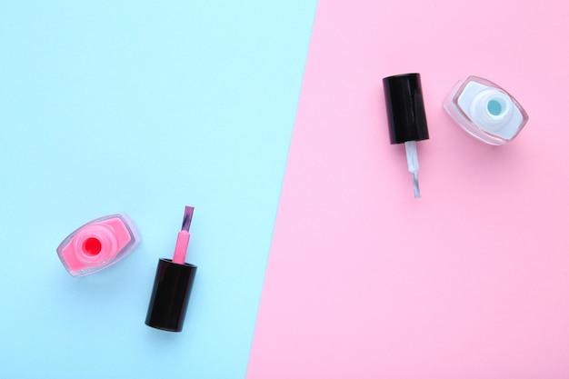 Esmaltes de uñas de color rosa y azul sobre fondo colorido