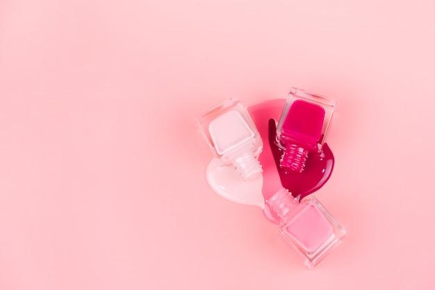 Los esmaltes de uñas gotean sobre una superficie rosa