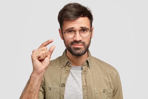 ¡eso es todo lo que tengo! modelo de joven barbudo disgustado da forma a algo pequeño con la mano