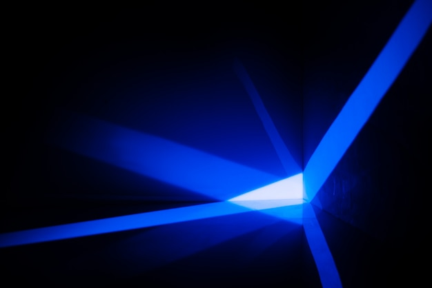 Espacio abstracto con rayos de luz azul en la pared