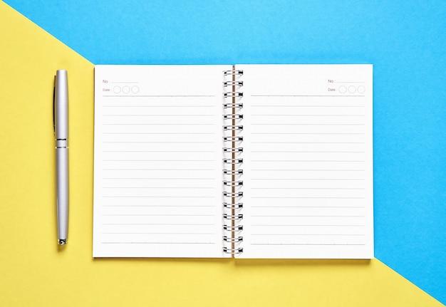 Espacio en blanco y pluma del cuaderno de la pantalla negra colocados en fondo amarillo y azul en colores pastel. adecuado para gráficos utilizados para publicidad.