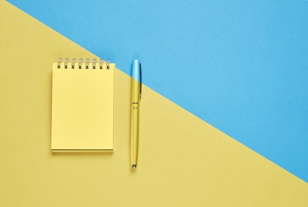 Espacio en blanco y pluma del cuaderno de la pantalla negra colocados en fondo amarillo y azul en colores pastel.