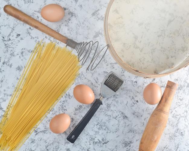 Espacio para cocinar. utensilios de cocina e ingredientes para cocinar en una mesa de hormigón blanco