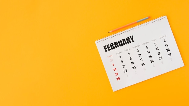 Espacio de copia amarillo de calendario de papelería de vista superior