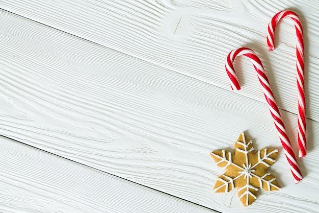 Un espacio de copia con cañas de azúcar y galletas de jengibre de navidad en forma de copo de nieve sobre fondo blanco de madera. vista superior.