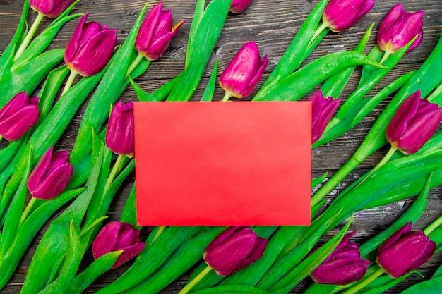 Espacio de copia del día de la mujer en tarjeta roja con tulipanes de color rosa brillante en el fondo