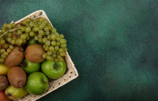 Espacio de copia de vista superior kiwi con manzanas verdes uvas y peras en una canasta sobre un fondo verde