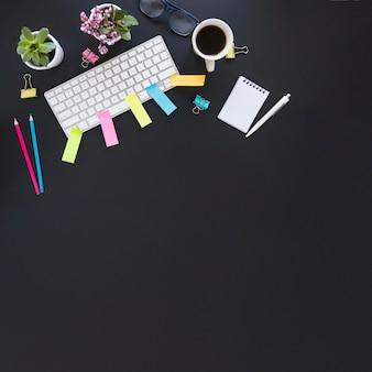 Espacio de trabajo con las plantas de la taza del teclado y estacionario