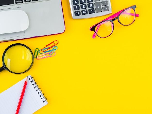 Espacio de trabajo de escritorio de vista superior con accesorios de oficina sobre fondo amarillo.