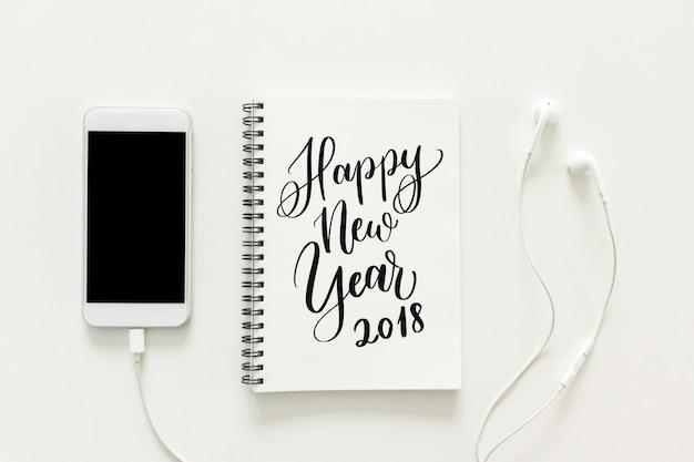"""Espacio de trabajo mínimo - foto creativa de la endecha plana del escritorio del espacio de trabajo con """"2018 feliz año nuevo"""" en sketchbook y teléfono móvil con la pantalla en blanco y el auricular en el fondo blanco. vista superior, concepto de año nuevo."""