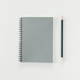 Espacio de trabajo mínimo - foto plana estable creativa de escritorio de espacio de trabajo con cuaderno de dibujo y lápiz de madera sobre fondo blanco de espacio de copia. vista superior, fotografía plana.