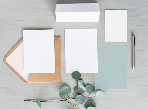 Espacio de diseño en blanco papeles y sobres sobre fondo gris