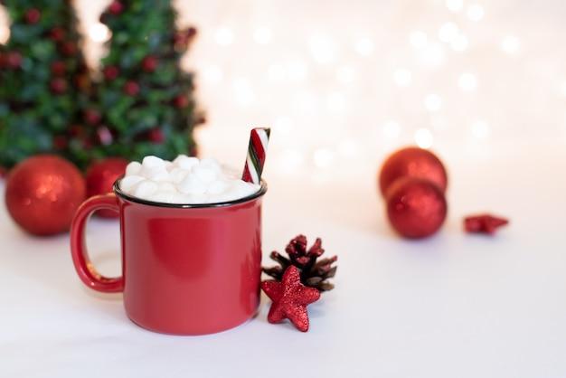 Espacio de escritorio de madera taza roja y árbol de navidad