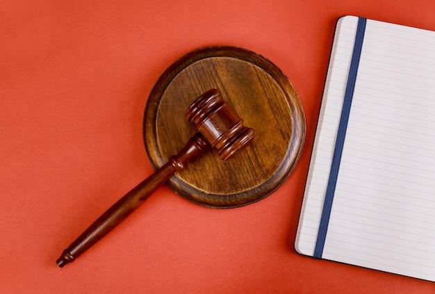Espacio de trabajo para abogado con mazo de juez en el bloc de notas de abogado sobre una mesa roja