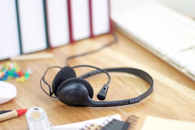 Espacio de trabajo con auriculares y equipos de oficina sobre fondo de trabajo de escritorio de madera