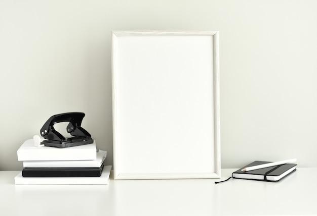 Espacio de trabajo en blanco y negro, marco de fotos en blanco, material de oficina.