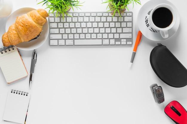 Espacio de trabajo blanco con papelería de oficina y desayuno.
