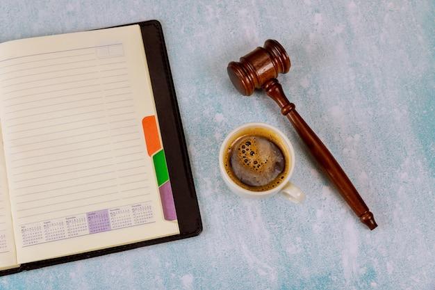 Espacio de trabajo con bloc de notas en blanco juez law martillo en una taza de café exprés