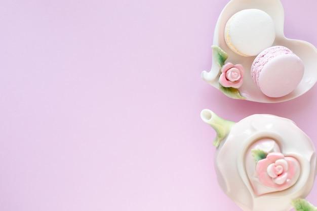 Espacio de trabajo de blogger de moda con laptop y accesorios femeninos, productos cosméticos en mesa de color rosa pálido.