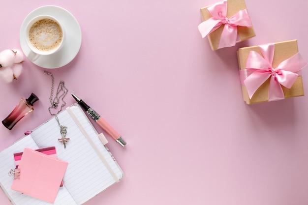 Espacio de trabajo de blogger de moda con laptop y accesorios femeninos, productos cosméticos en mesa rosa.