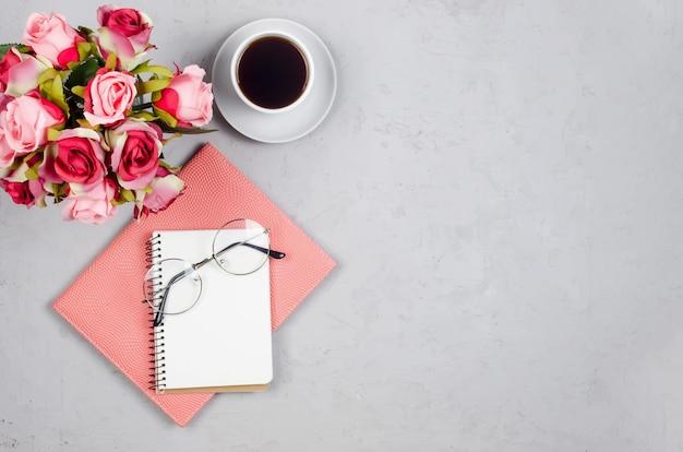 Espacio de trabajo de blogger o autónomo con tulipanes, cuaderno, reloj y vacío