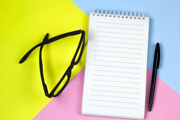 Espacio de trabajo brillante vista superior, maqueta hoja de cuaderno vacía, gafas
