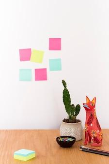 Espacio de trabajo con cactus en maceta y estatuilla en escritorio.