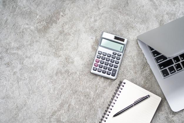 Espacio de trabajo con calculadora, bolígrafo, portátil en el fondo de piedra de roca.