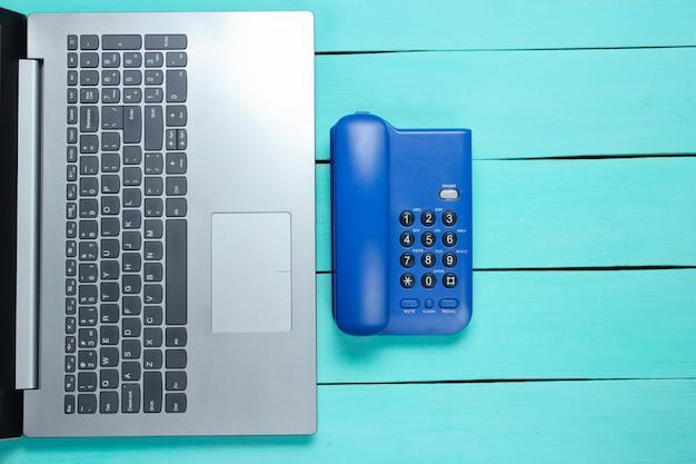 Espacio de trabajo call center. ordenador portátil, teléfono de la oficina en una mesa de madera azul.