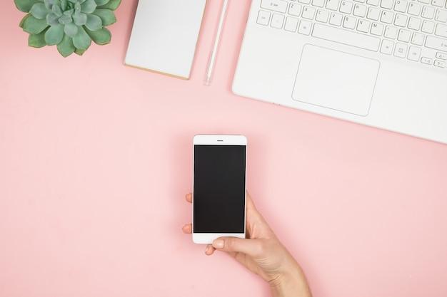 Espacio de trabajo en casa para mujeres. girl blogger trabaja con teléfono y computadora portátil. concepto independiente. mensajes de texto de teletrabajadores usando laptop e internet, trabajando en línea.