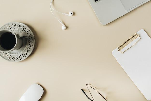 Espacio de trabajo con computadora portátil, auriculares, mouse, taza de café, portapapeles y gafas en superficie beige